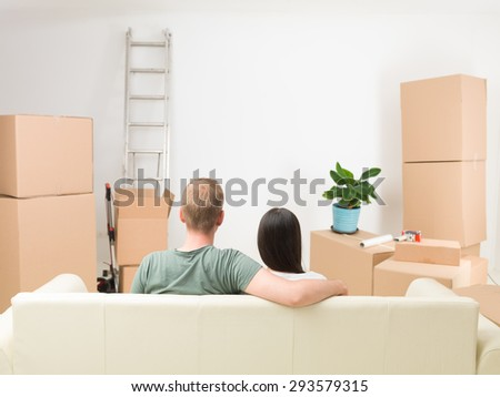 rear view of couple sitting on sofa after moving in new house - stock photo