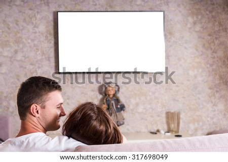 Rear View of Couple Snuggling Together on Sofa While Watching Flat Screen Television Mounted on Living Room Wall, View of Back of Heads on Romantic Date Night - Screen is Blank for Copy - stock photo