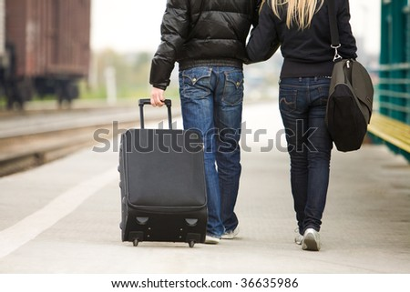 Rear view of couple walking down train station with their baggage - stock photo