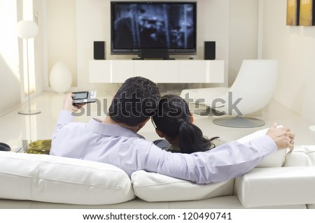 Rear view of couple watching TV while sitting on sofa - stock photo