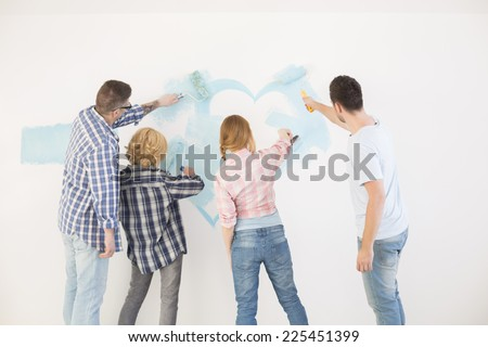 Rear view of couples painting wall in new home - stock photo
