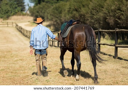 rear view of cowboy walking with his horse - stock photo