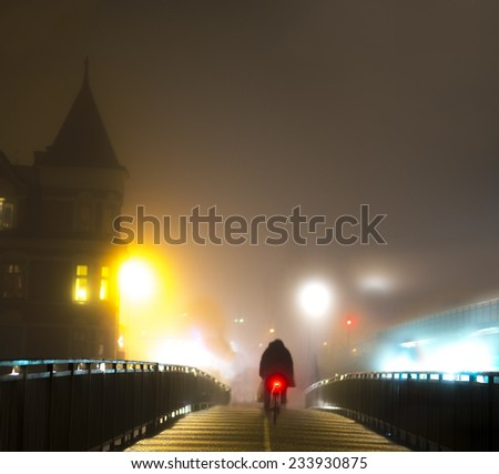 Rear view of cyclist on bridge on foggy night - stock photo