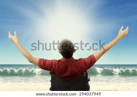 Rear view of disabled young man enjoy freedom while sitting on wheelchair and raise hands up at beach - stock photo
