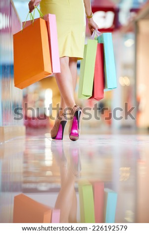Rear view of elegant shopaholic with shopping bags leaving the mall - stock photo