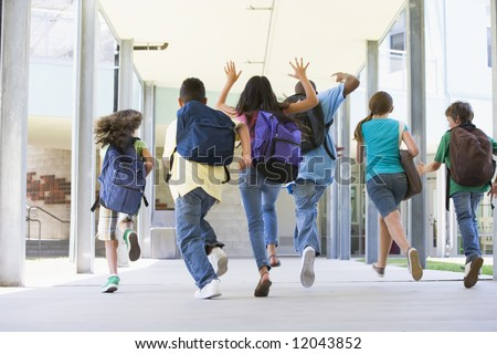 Rear view of elementary school pupils running outside - stock photo