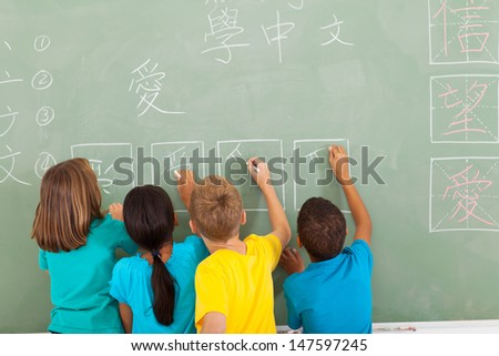 rear view of elementary school students learning chinese writing on chalkboard - stock photo
