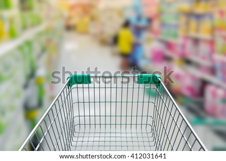rear view of empty shopping cart with shopping mall or grocery background - stock photo