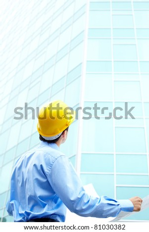 Rear view of engineer looking at office building - stock photo