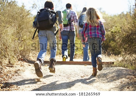 Rear View Of Family Hiking In Countryside Wearing Backpacks - stock photo