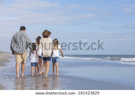 Rear view of family mother, father, daughter, parents and female girl children walking in the sea on a beach  - stock photo