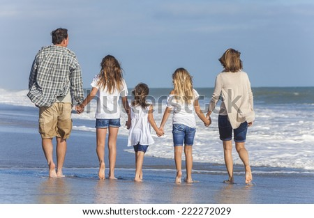 Rear view of family mother, father, daughter, parents and female girl children walking in the sea on a beach