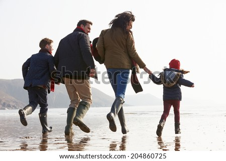 Rear View Of Family Running Along Winter Beach