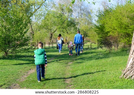 Rear View of Family Walking Together Outdoors on Overgrown Dual Track Country Road Through Green Trees