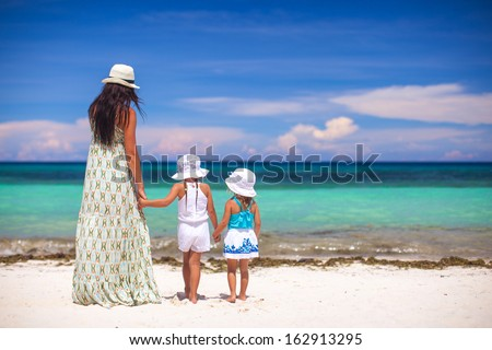 Rear view of fashion young mother and two her kids at exotic beach on sunny day - stock photo