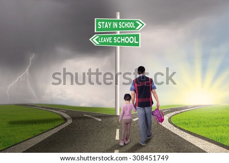 Rear view of father and his daughter walking on the road with road sign to stay or leave school - stock photo