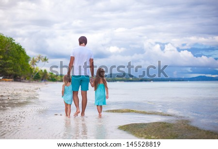 Rear view of father and his two little daughters walking by the sea
