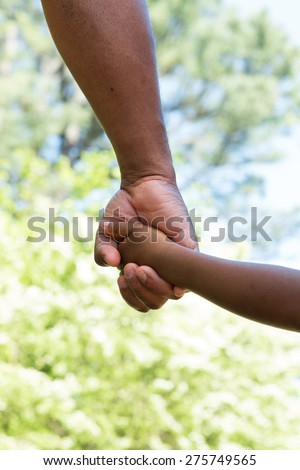 Rear view of father and son holding hands.