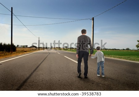 rear view of father and son walking on a street - stock photo