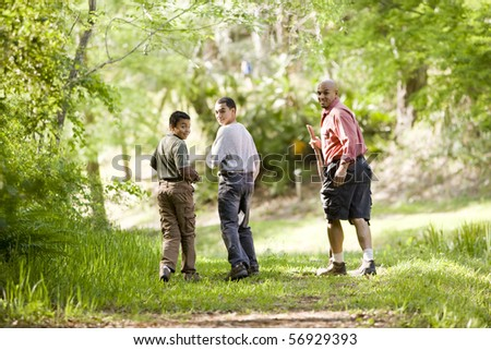 Rear view of father and two sons hiking on trail in woods, 10 and 14 years old - stock photo
