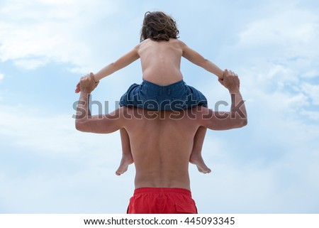 Rear view of father holding son hands while carrying him against sky - stock photo