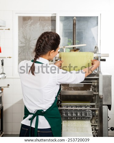 Rear view of female chef processing pasta sheet in automated machine at commercial kitchen - stock photo