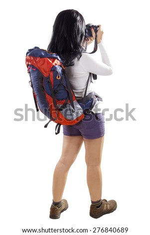 Rear view of female hiker taking picture with a digital camera while carrying rucksack, isolated on white background - stock photo