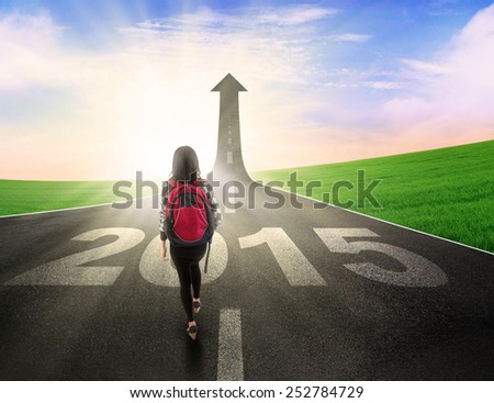 Rear view of female student walking on the road to future