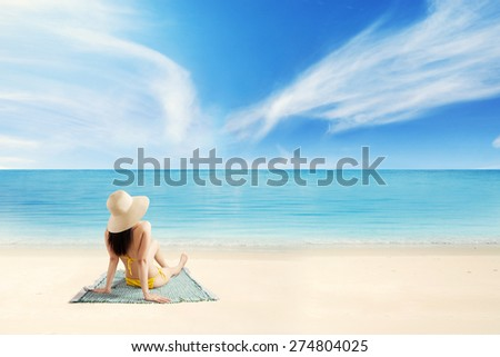 Rear view of female tourist wearing bikini and hat on the beach, sitting on mat while enjoying holiday - stock photo
