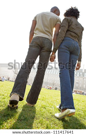 Rear view of figures of a man and woman holding hands while walking through London city on a sunny day. - stock photo