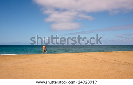 Rear view of fisherman on a wide sandy beach