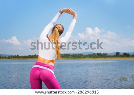 Rear view of fit young blonde Caucasian woman in pink and white sportswear stretching hands by the lake. Fitness girl with hands raised above her head stretching outdoors on sunny summer day. - stock photo