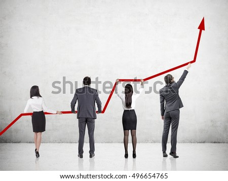Rear view of four businesspeople holding red graph near concrete wall. Concept of company growth. Mock up
