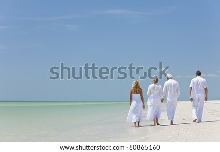 Rear view of four people, two seniors, couples or family generations, holding hands, walking on a tropical beach - stock photo