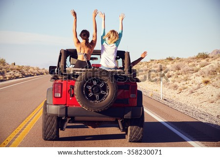 Rear View Of Friends On Road Trip Driving In Convertible Car - stock photo