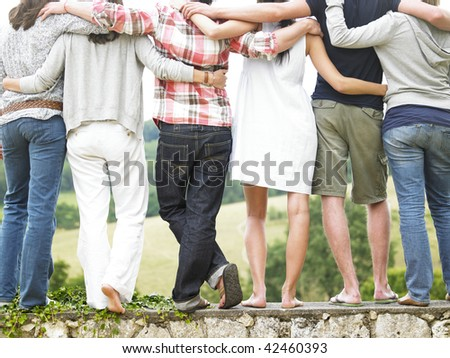 Rear view of friends standing on stone wall. Vertical. - stock photo