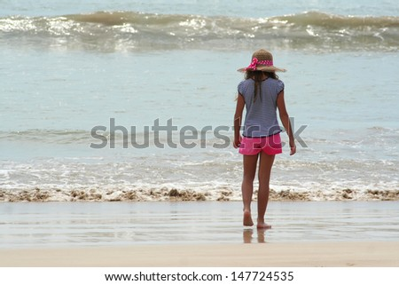 Rear view of Girl on the ocean coast - stock photo