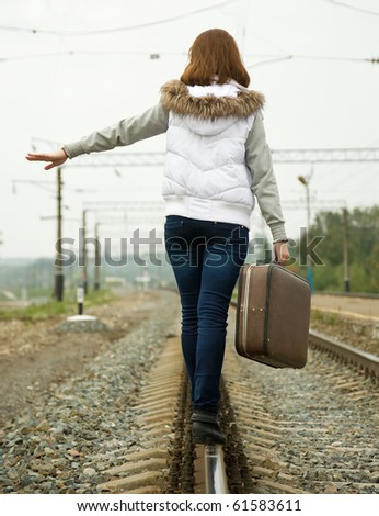 Rear view of girl with suitcase walking along  rail - stock photo
