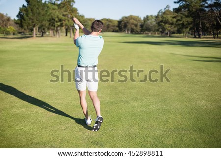 Rear view of golfer taking shot while standing on field