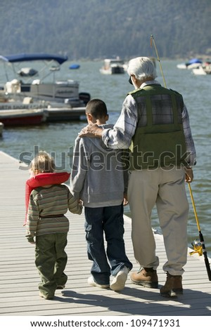Rear view of grandfather walking with his grandsons on pier - stock photo