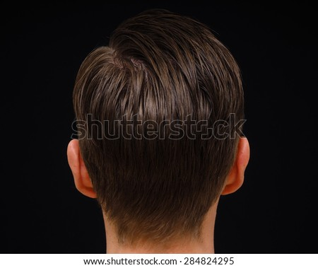 Rear view of hairstyle on male person with brown hair at closeup isolated towards black background - stock photo