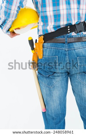 Rear view of handyman wearing tool belt while holding hard hat on white background - stock photo