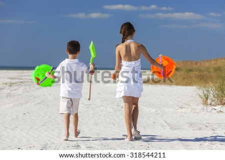 Rear view of happy children, boy girl, brother and sister having fun playing in the sand on a beach with bucket and spade