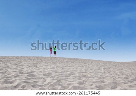 Rear view of happy children enjoy holiday together and jump on desert at Volcano Bromo - stock photo