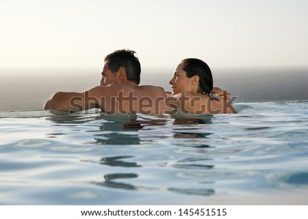 Rear view of happy couple relaxing in infinity pool at resort - stock photo