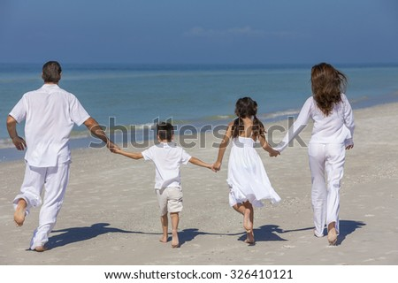 Rear view of happy family of mother, father and two children, son and daughter, running holding hands and having fun in the sand of a sunny beach