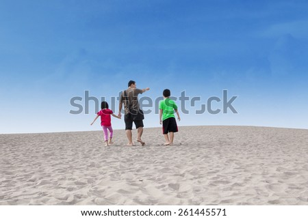 Rear view of happy family walking on the sand dune under a blue sky - stock photo