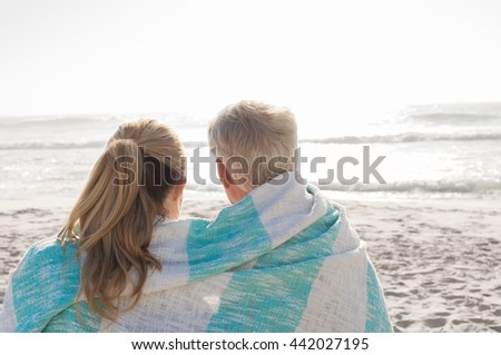 Rear view of happy mature couple looking at sunset at the beach. Back view of loving senior couple embracing at beach wrapped in towel. Retired couple in love relaxing at seaside. - stock photo