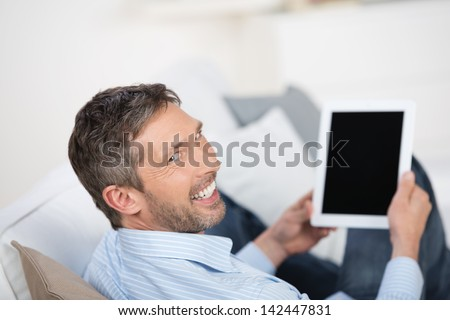 Rear view of happy mature man holding tablet pc on sofa at home - stock photo
