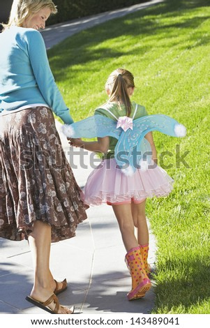 Rear view of happy mother with daughter in fairy costume walking on path at park - stock photo